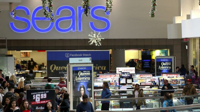 Shoppers walk outside the Sears store at Woodfield Mall in Schaumburg, on Black Friday, Nov. 23, 201