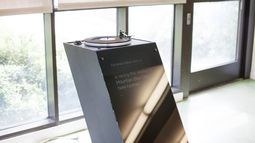 A digital monument by Gabriel Barcia-Colombo use a record player to project a deceased person's Facebook status updates.