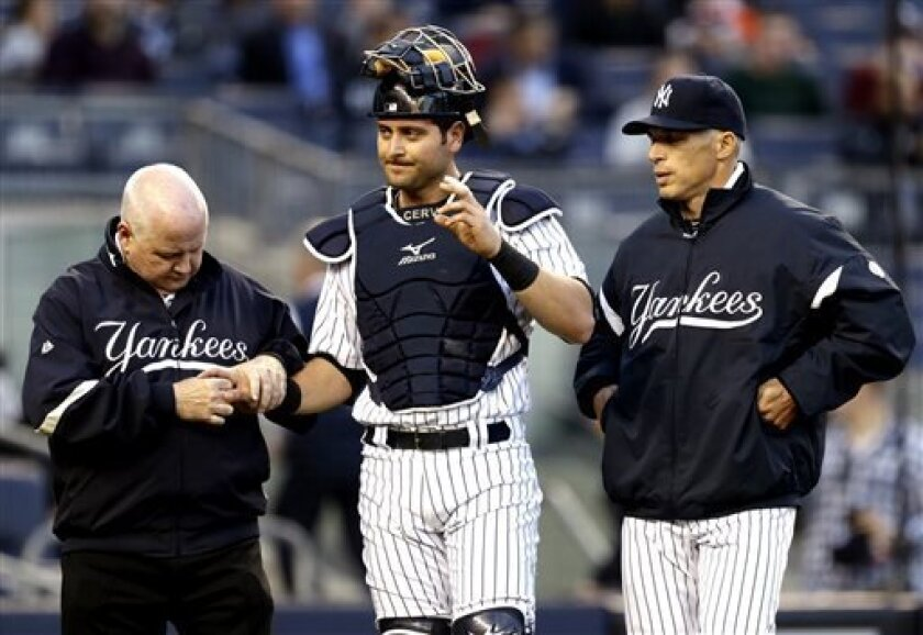 New York Yankees trainer Steve Donohue, left, checks on catcher Francisco Cervelli, center, as manager Joe Girardi looks on during the first inning of a baseball game against the Toronto Blue Jays at Yankee Stadium in New York, Friday, April 26, 2013. Cervelli left the game. (AP Photo/Julio Cortez)