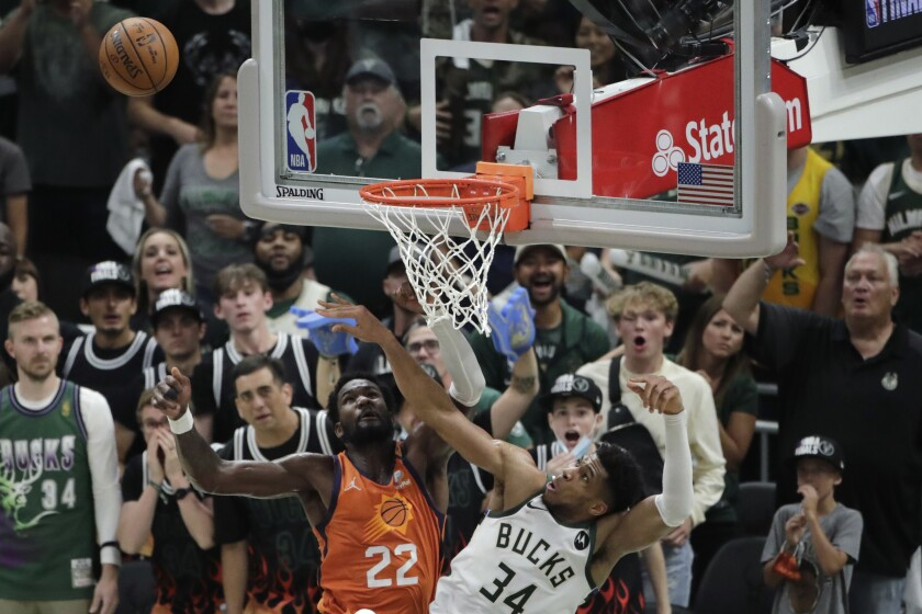 Milwaukee Bucks forward Giannis Antetokounmpo (34) blocks a shot by Phoenix Suns center Deandre Ayton (22) during the second half of Game 4 of basketball's NBA Finals Wednesday, July 14, 2021, in Milwaukee. (AP Photo/Aaron Gash)