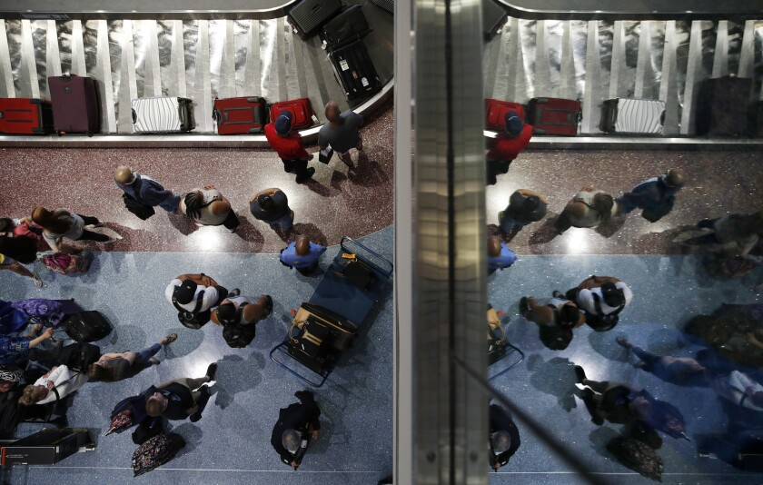In this June 29, 2018, photo, passengers wait for baggage at McCarran International Airport in Las Vegas. As summer vacationers start to pack up and head home, Congress is considering a sweeping tally of proposals that could affect travelers, from dictating seat size and legroom to rolling back rules that require airlines to advertise the full price of a ticket.