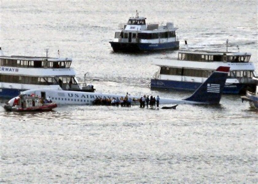 In this Jan. 15, 2009 file photo, passengers and crew aboard US Airways Flight 1549 await rescue by a New York City Fire Department boat and a group of private ferries after the aircraft made and emergency landing on the Hudson River off the coast of New York, Thursday, Jan. 15, 2009. After the pilot successfully landed his aircraft in the frigid water, the first rescuers on the scene were not police or the U.S. Coast Guard, but a handful of ferries that offer visitor tours and shuttle commuters between New Jersey and Manhattan. (AP Photo/Steven Day)
