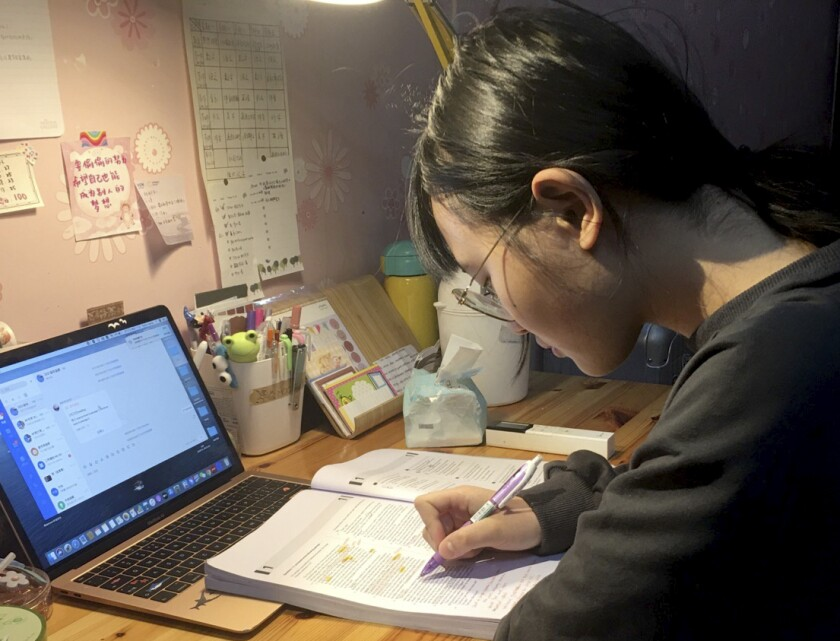 In this Feb. 27, 2020 photo provided by Zhang Qingqing, high school junior Zhang Qingqing studies at home in Chongqing, a megacity in southwest China. Zhang was planning to take the SAT, an exam that foreign students must take to enroll in American universities, in Thailand this month before it was canceled due concerns over the coronavirus. Universities that rely on international enrollment are expected to take a big hit in the next academic year as canceled entrance exams and travel restrictions in China because of the virus make it impossible for students to enroll and attend college. (Zhang Qingqing via AP)