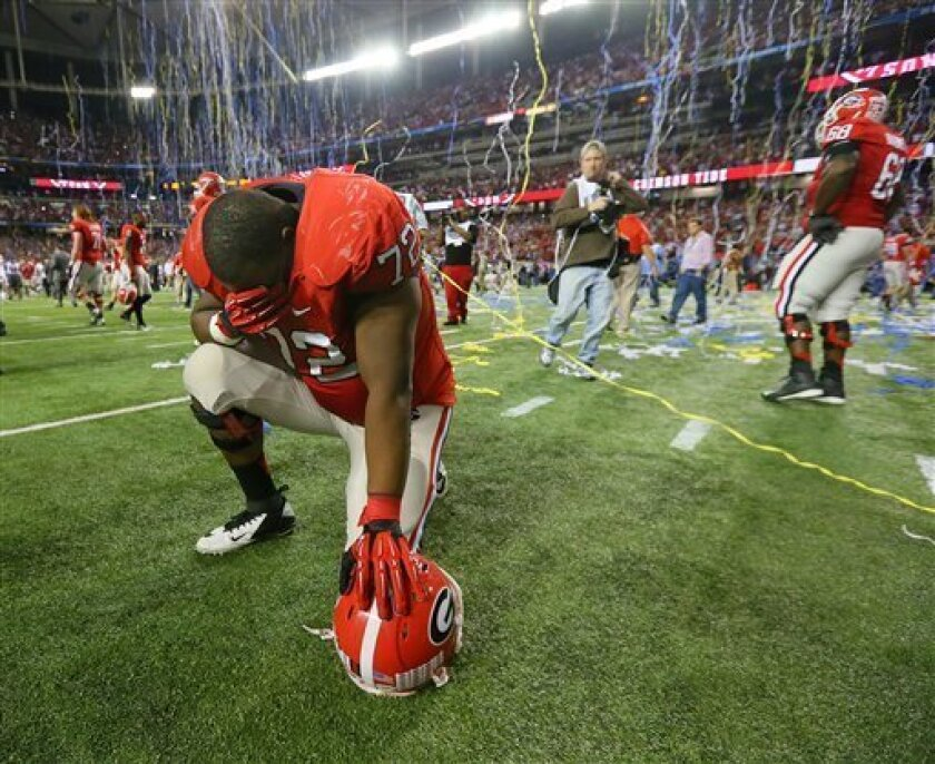 Georgia offensive lineman Kenarious Gates is dejected as the confetti falls after their 32-28 loss to Alabama in the Southeastern Conference championship NCAA college football game, Saturday, Dec. 1, 2012, in Atlanta. (AP Photo/Atlanta Journal-Constitution, Curtis Compton) MARIETTA DAILY OUT; GWINNETT DAILY POST OUT; LOCAL TV OUT; WXIA-TV OUT; WGCL-TV OUT