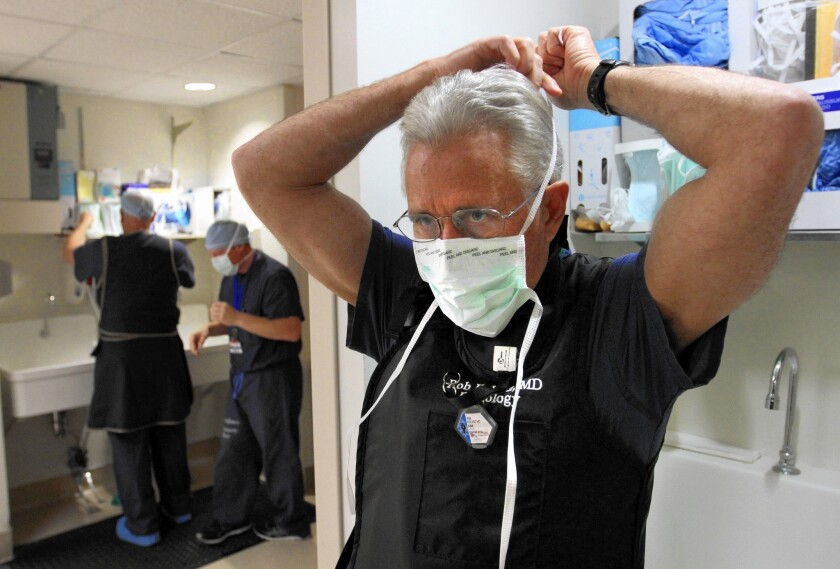 Dr. Robert Kolanz, right, dons a sterile mask at Providence Little Company of Mary Medical Center in Torrance, which earned an A grade for patient safety.