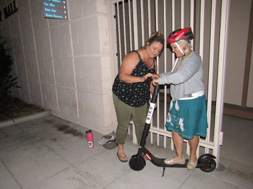 Liberty Brown (left) and Knikki Royster check out a Bird scooter outside of City Hall in La Mesa last year. Several hundred of the motorized scooters landed in La Mesa last August but have since been removed.
