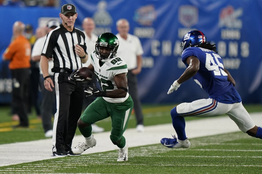 New York Jets wide receiver Jamison Crowder (82) runs the ball next to New York Giants cornerback Madre Harper (45) during the first half of an NFL preseason football game Saturday, Aug. 14, 2021, in East Rutherford, N.J. (AP Photo/Corey Sipkin)
