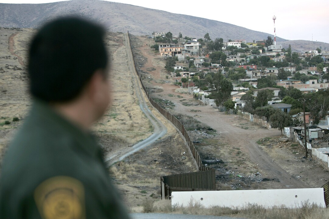 This file photo shows Border Patrol agent Michael Jimenez looking at a Tijuana colonia in the shadow of Otay Mountain.