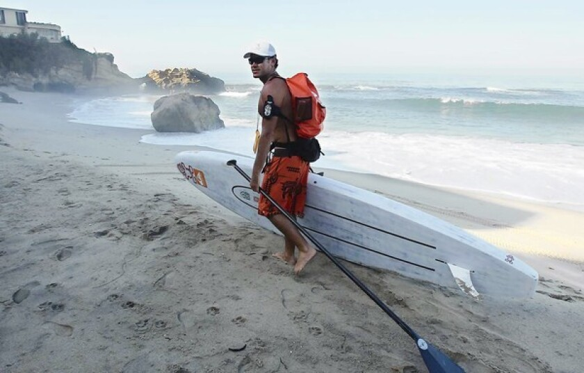 James Pribram says bon voyage as he hauls his stand-up paddleboard and gear at Pearl St. beach where he embarks on a paddle journey along the Southern California coast to Mexican border in an effort to bring awareness to rivermouth pollution along the way.