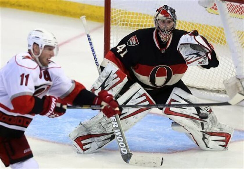 Ottawa Senators goaltender Craig Anderson (41) watches the puck as Carolina Hurricanes' Jordan Staal tries to deflect a shot during the third period of their NHL hockey game in Ottawa, Ontario, Tuesday, April 16, 2013. The Senators won 3-2. (AP Photo/The Canadian Press, Fred Chartrand)