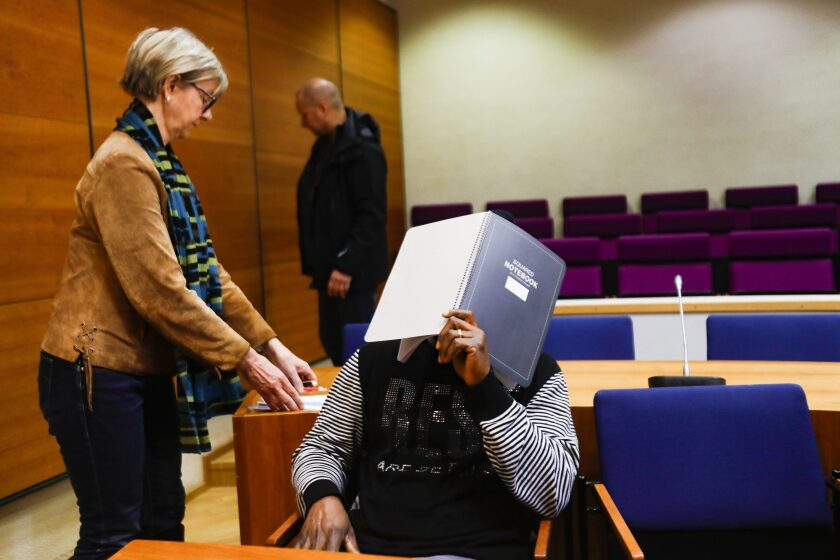 A 50-year old Sierra Leone man suspected of committing war crimes and crimes against humanity from 1999 through 2003 during Liberia's civil war, hides his face at the custody hearing at the Pirkanmaa District Court in Tampere, Finland, on Thursday March 12, 2020. The accused man is not publicly named, facing accusations of several murders, gross human rights abuses in exceptional circumstances, aggravated war crimes and an aggravated rape. (Mika Kanerva/Lehtikuva via AP)