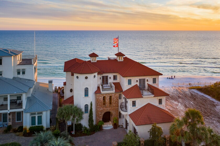 The three-story home includes six bedrooms, nine bathrooms, five balconies and a rooftop deck overlooking the beach.