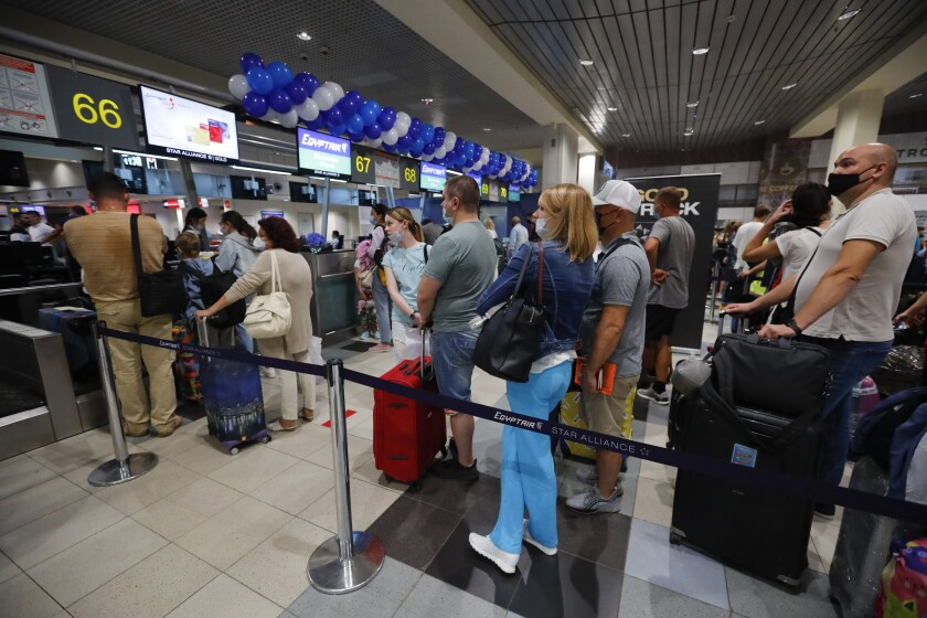 Russian tourists gather at the Egyptair check-in desk at the Domodedovo International Airport outside Moscow, Russia, Monday, Aug. 9, 2021. The Russian state aviation agency, Rosaviatsiya, has cleared eight Russian airlines to operate flights to Hurghada and Sharm El Sheikh from 43 cities all across Russia. (AP Photo/Alexander Zemlianichenko Jr)