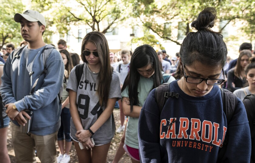 Mourners observe a moment of silence during a vigil for University of Texas at Austin student Haruka Weiser on the campus Thursday.