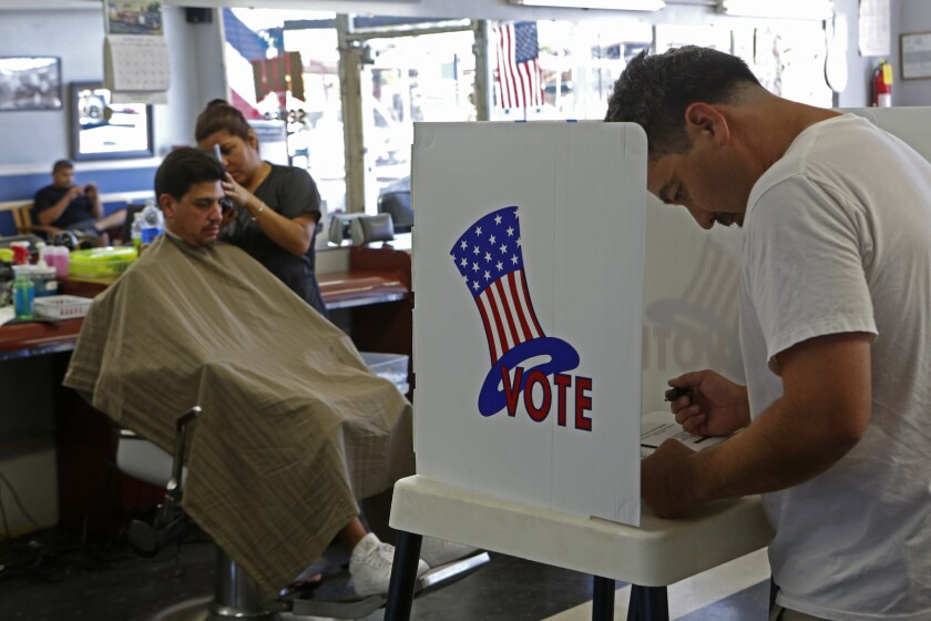Big donors dominated in California congressional primaries, a watchdog group's report says. Here, a voter casts his ballot in a Long Beach barber shop on June 3.