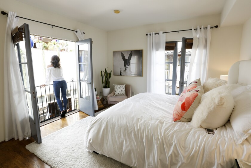 KTLA News anchor Megan Henderson stands on the Juliet balcony in her master bedroom.