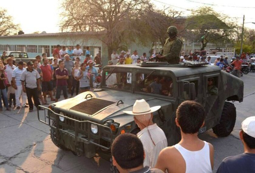 Mexican soldiers enter a village in Michoacan state during an operation to take control of areas where drug cartels threaten the population.