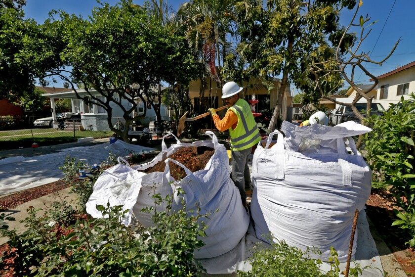 Workers remove topsoil from homes in Boyle Heights in 2015 as part of the state-led cleanup.