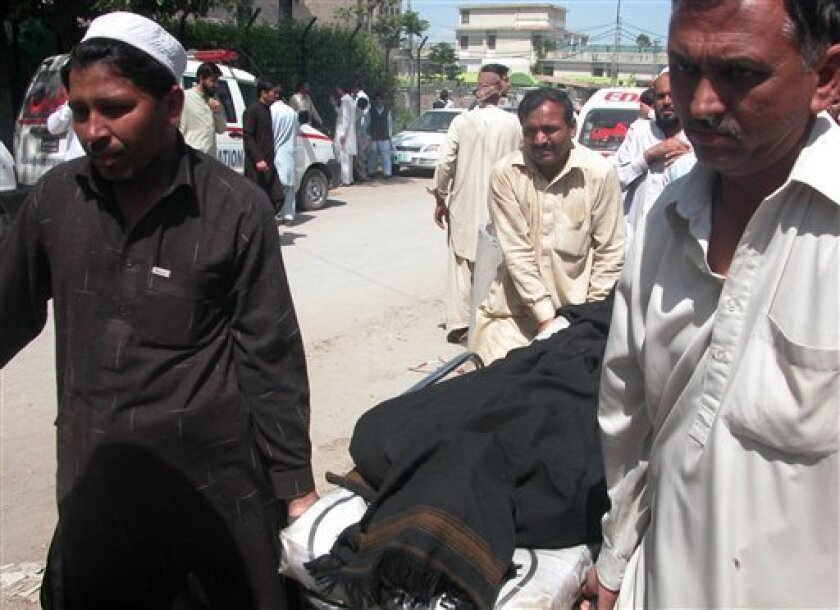 People carry the body of a person killed in an attack, in Peshawar, Pakistan on Tuesday, April 2, 2013. Several dozen militants armed with assault rifles and rocket-propelled grenades attacked a power grid station in northwestern Pakistan before dawn Tuesday, killing many people and taking hostages, police said. (AP Photo/Nasir Khan)