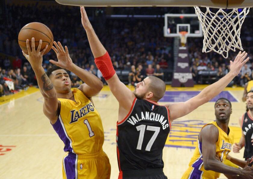 Lakers guard D'Angelo Russell, left, shoots as Toronto center Jonas Valanciunas defends on Friday night.