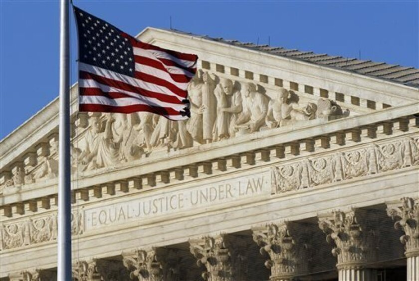 FILE - In this June 27, 2012 file photo, an American flag flies in front of the Supreme Court in Washington. DNA may be the building blocks of life, but can something taken from it be the building blocks of a multimillion-dollar medical monopoly? The Supreme Court will grapple with that question Mo