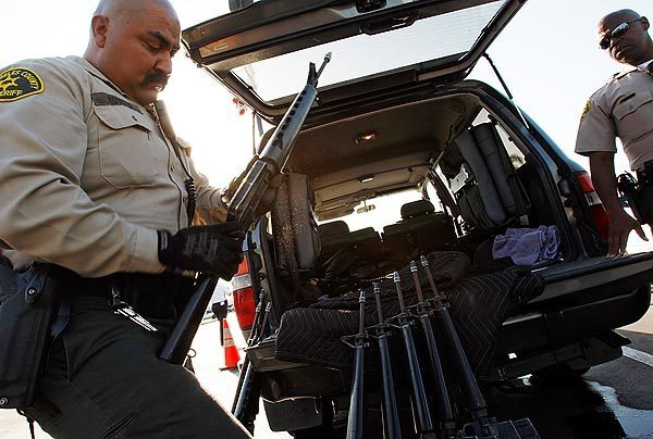 """Los Angeles County sheriff's deputies inspect and inventory about a dozen civilian versions of military assault rifles during the annual """"gift for guns"""" exchange program in Compton. One man turned in dozens of weapons."""