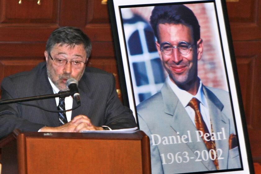 Dr. Judea Pearl, father of Daniel Pearl, speaks near a portrait of the slain American journalist in Miami Beach in 2007.