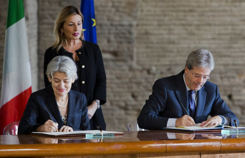 Unesco Director General Irina Bokova, left, and Italian Foreign Minister Paolo Gentiloni  sign an agreement during the presentation of the Unite for Heritage operation in Rome, Tuesday, Feb. 16, 2016. Italy is forming a task force using paramilitary police art experts to prevent the looting and des