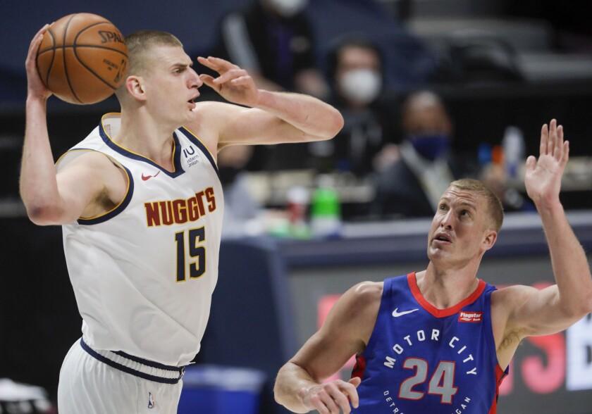 Denver Nuggets center Nikola Jokic (15) passes around Detroit Pistons center Mason Plumlee (24) in the first quarter of an NBA basketball game in Denver, Tuesday, April 6, 2021. (AP Photo/Joe Mahoney)