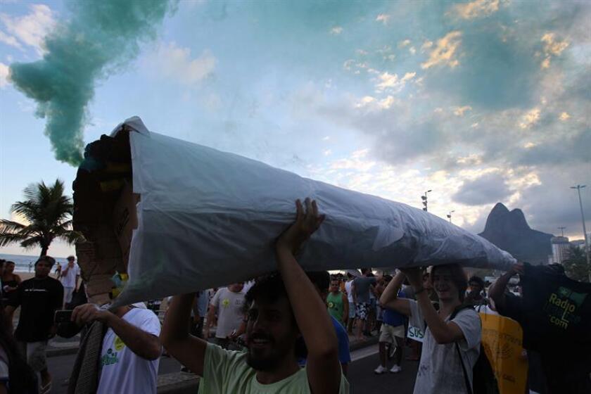 Manifestantes en favor de la legalización de la marihuana cargan un cigarrillo que imita un porro gigante durante la Marcha Mundial de la Marihuana en la playa de Ipanema, en Río de Janeiro (Brasil). EFE/Archivo
