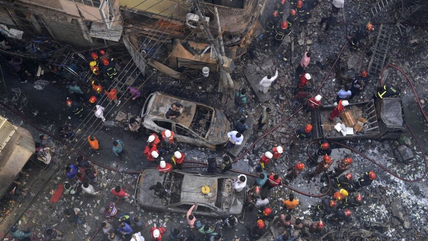 Rescuers stand at the site of a late Wednesday night fire in Dhaka, Bangladesh, Thursday, Feb. 21, 2
