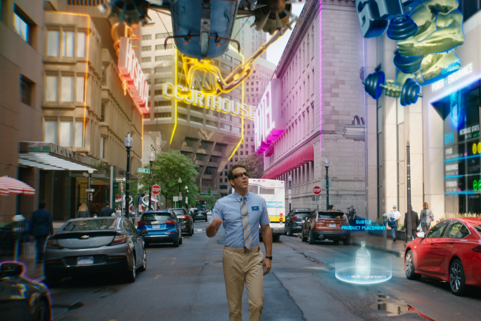 Ryan Reynolds walks down a street lit up with neon signs.
