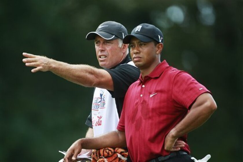 """In this Sept. 27, 2009, photo, Tiger Woods gets some direction from his caddie, Steve Williams, on the fifth fairway during the final round of The Tour Championship golf tournament in Atlanta. Williams said he knew nothing about the golfer's extramarital affairs and was angry with him over the scandal. Williams told TV3's """"60 Minutes"""" program in New Zealand on Wednesday, March 3, that he also is bitter at the reaction toward him from the media and members of the public. (AP Photo/Dave Martin)"""