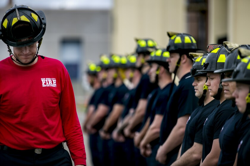 Instructor Charles Brookes lowers his head in front of recruits lined up during a fire academy in 2019.