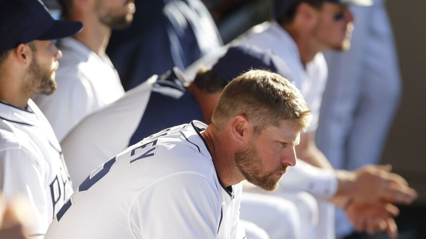 The Padres' Chase Headley, front right, and teammates sit in the dugout in the 12th inning of the Padres game against the Milwaukee Brewers on Opening Day at Petco Park in San Diego on Thursday.