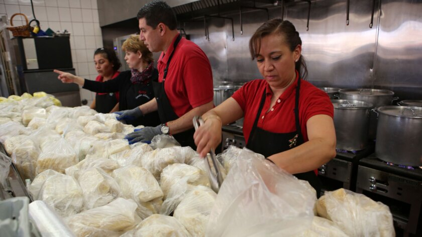 Lucy Garcia, right, and others make bags of holiday tamales for the Christmas Eve rush at Tamales Lilianas in East Los Angeles.