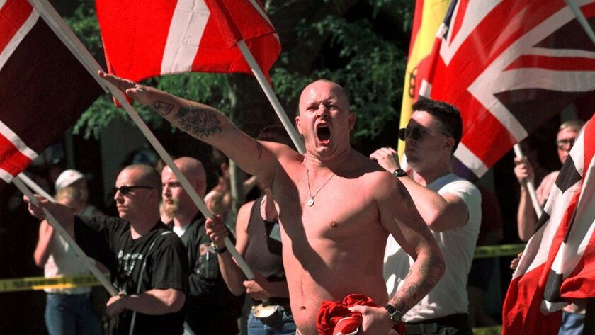 Karl Wolf raises his arm in a Nazi salute as he marches through the streets of Coeur d'Alene, Idaho, in July 1998.