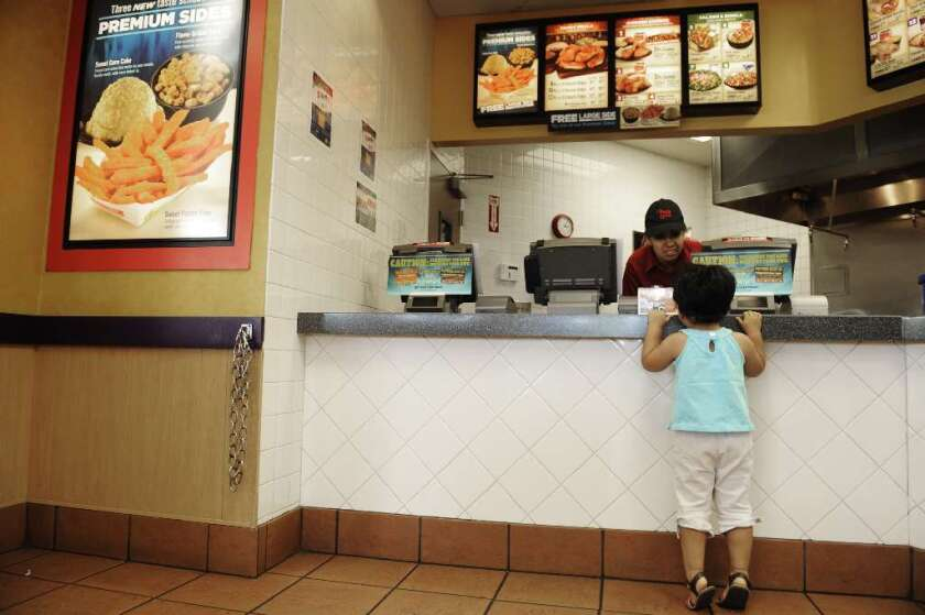 One-third of U.S. kids eat fast food on a typical day, according to a new report from the Centers for Disease Control and Prevention. Above, a little girl requests a packet of sauce at an El Pollo Loco restaurant in Santa Ana.
