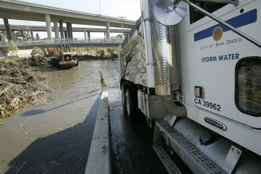 In this file photo, San Diego city storm water crews clean the channel next to the train tracks on Roselle Street in Sorrento Valley in preparation for heavy rain.