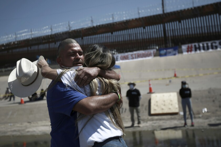 """Family members embrace during the 8th annual """"Hugs not Walls"""" event on the Rio Grande, in Ciudad Juarez, Mexico, Saturday, June 19, 2021. The event allows migrants living in the U.S. to reunite with their relatives living on the other side of the border for a few minutes. (AP Photo/Christian Chavez)"""