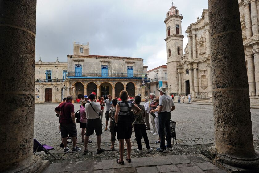 Tourists visit the Old Havana section of Cuba's capital. The U.S. further eased travel and trade restrictions with Cuba on Tuesday.