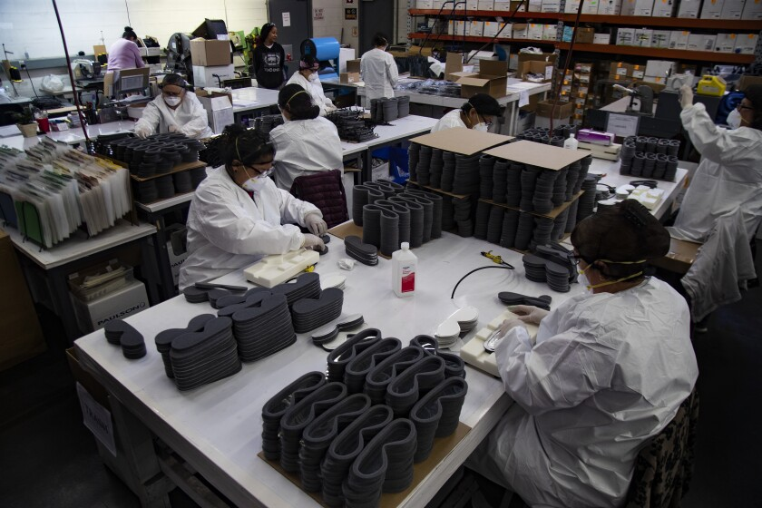 Workers at Paulson Manufacturing in Temecula, Calif., assemble medical goggles for shipment to China to help prevent the spread of the coronavirus.