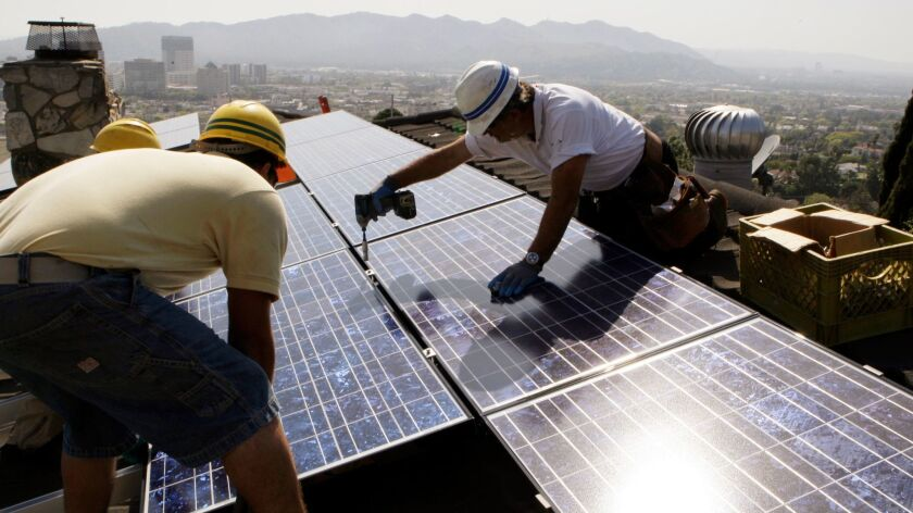 Workers install solar electrical panels on the roof of a home in Glendale, Calif. on March 23, 2010.