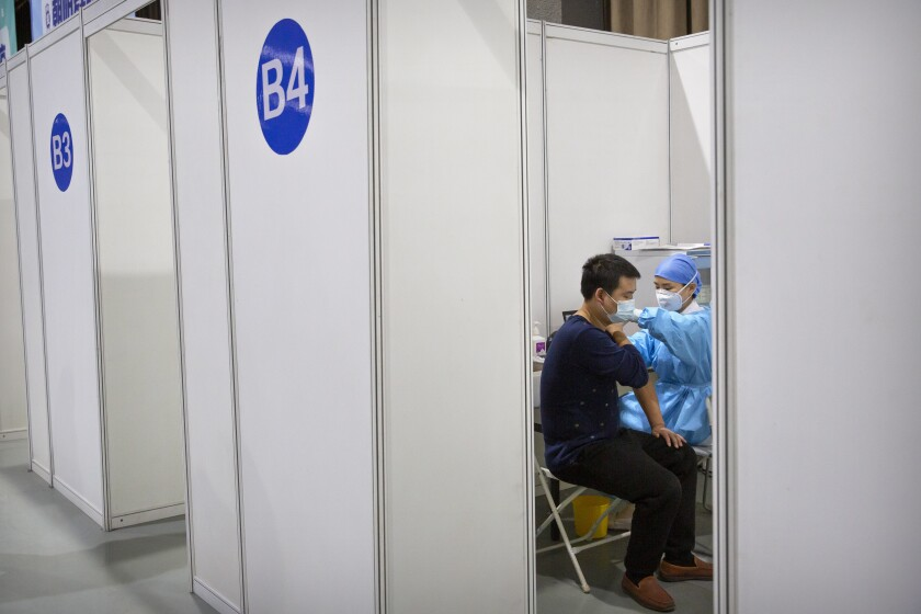 Una trabajadora médica administra la vacuna contra el coronavirus a un paciente en Beijing.