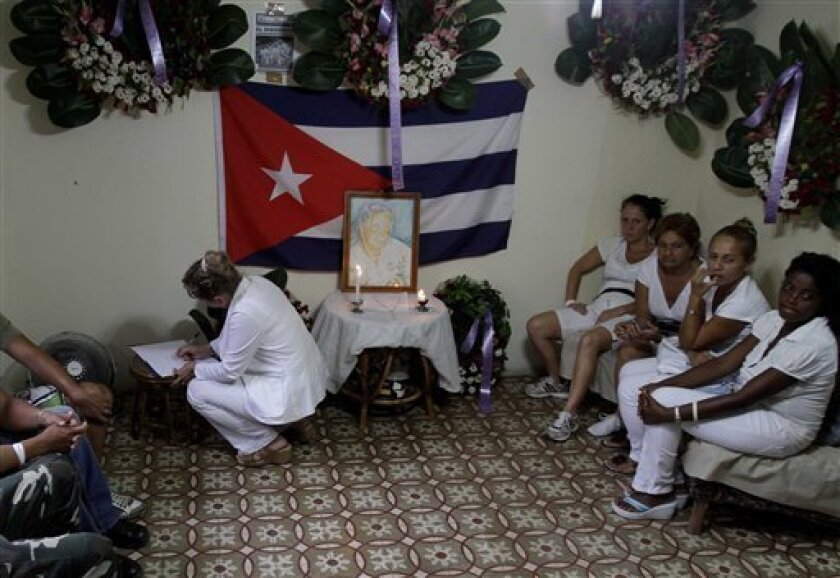 """People gather to pay tribute to Laura Pollan, the late leader of the dissident group """"Ladies in White,"""" in Pollan's home in Havana, Cuba, Saturday Oct. 15, 2011. According to Elizardo Sanchez, head of the Cuban Commission for Human Rights and National Reconciliation, Pollan died of a cardio-respiratory attack on Friday, Oct 14, 2011. (AP Photo/Franklin Reyes)"""