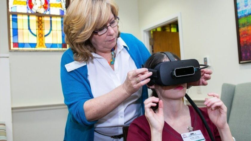 Ann Brennan, director of volunteer services for Chicago Methodist Senior Services, puts a virtual reality headset on Amber Davis at Hartwell Place in Andersonville, as she prepares to go through a lab designed to help caregivers understand how it feels to live with dementia.