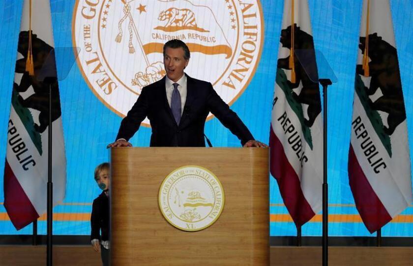 El gobernador de California, Gavin Newsom (c), habla mientras su hijo Dutch (i), de dos años, se asoma por detrás del podio tras caminar en el escenario mientras Newsom hablaba durante su ceremonia de inauguración, en el Capitolio del Estado, en Sacramento (EE.UU.). EFE/Archivo