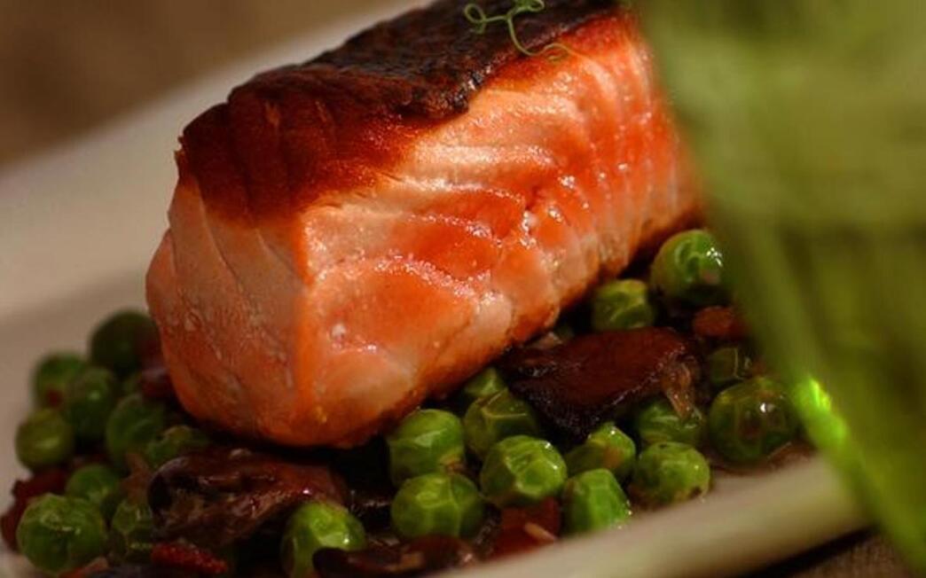 Crispy-skinned wild salmon with braised spring peas and mushrooms