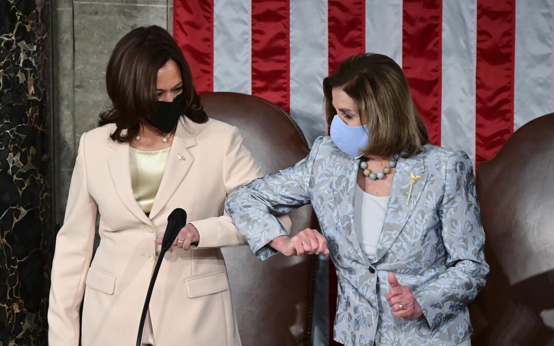 Two women bump elbows.