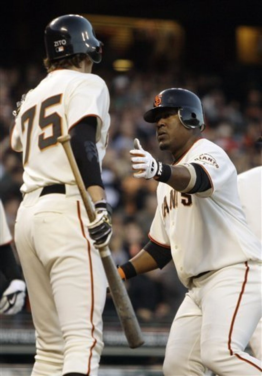 San Francisco Giants' Juan Uribe, right, celebrates his two-run home run with pitcher Barry Zito (75) in the fifth inning of a baseball game against the Florida Marlins on Tuesday, July 7, 2009, in San Francisco. (AP Photo/Ben Margot)